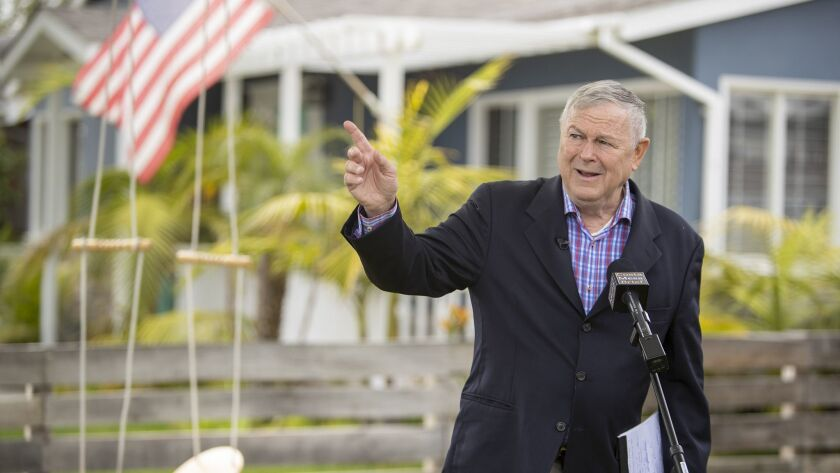 Rep. Dana Rohrabacher points to an commercial aircraft that can be heard leaving John Wayne Airport