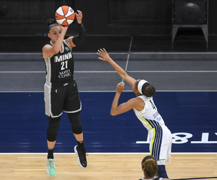 Minnesota Lynx guard Kayla McBride (21) scores a 3-point basket while being defended by Dallas Wings guard Moriah Jefferson (4) during the first half in a WNBA basketball game Wednesday, July 7, 2021, in Minneapolis. (Aaron Lavinsky/Star Tribune via AP)