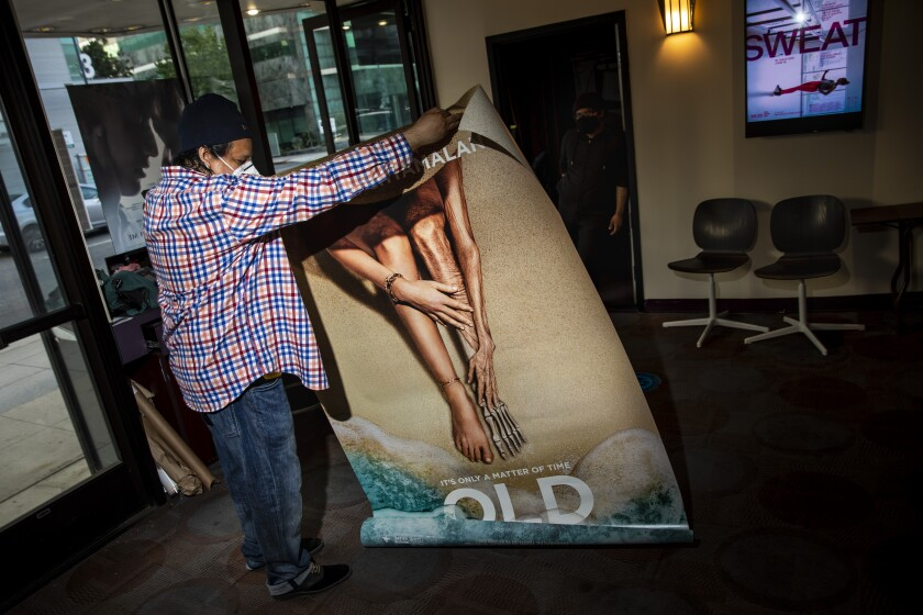 """Humberto Sandoval unrolls a poster for director M. Night Shyamalan's film """"Old,"""""""