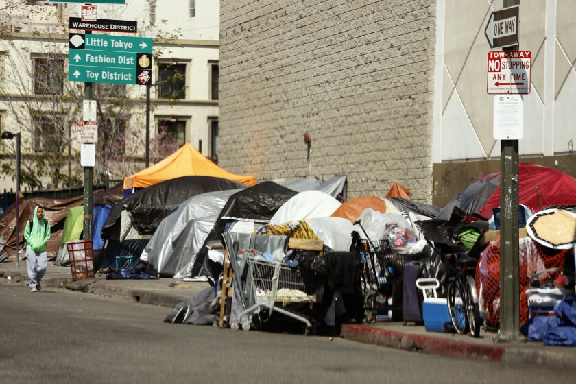 A man walks along a row of tents and enclosures in skid row on March 26.