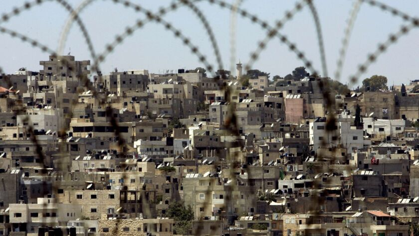 The Palestinian refugee camp of Kalandia is seen through razor–wire near the West Bank city of Ramal