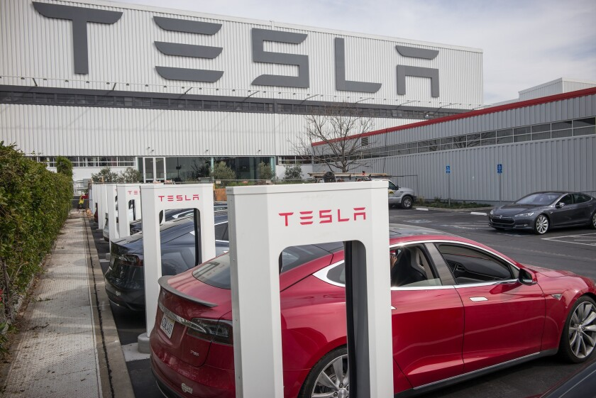 Cars charge at stations outside of Tesla's factory in Fremont.