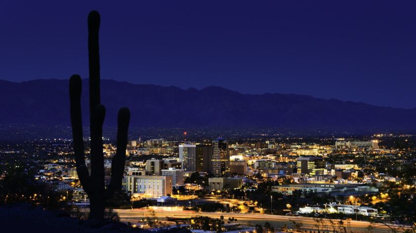 Tucson Arizona at night framed by saguaro cactus and mountains