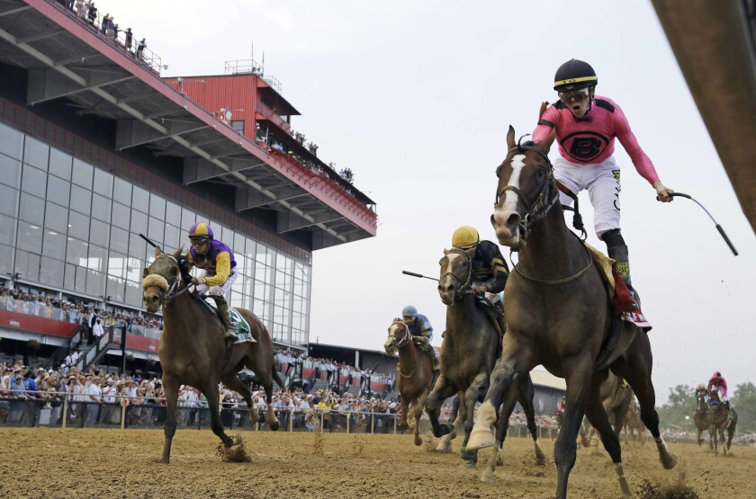 FILE - In this May 18, 2019, file photo, jockey Tyler Gaffalione, right, reacts aboard War of Will, as they crosses the finish line first to win the Preakness Stakes horse race at Pimlico Race Course in Baltimore. The owners of the historic racetrack that hosts the Preakness Stakes and Baltimore officials have reached an agreement to keep the Triple Crown series' middle jewel in the city. (AP Photo/Steve Helber, File)