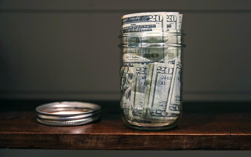 A jar filled with $20 bills