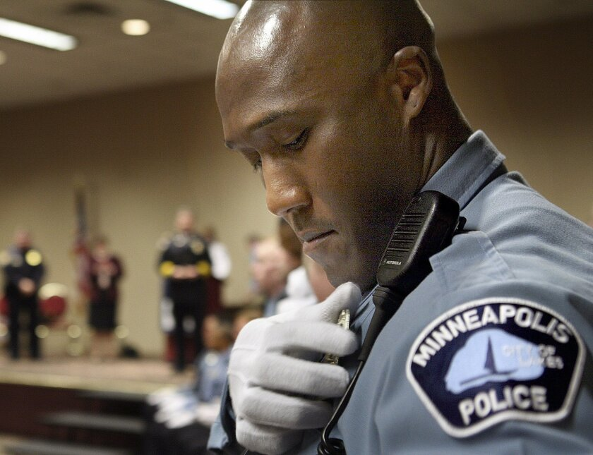 In this March 15, 2007 photo, Minneapolis Police Department Academy graduate Michael Griffin pins his badge onto his uniform during a graduation ceremony in Minneapolis. An indictment Wednesday, May 20, 2015, accuses Griffin of assaulting several people while off-duty and filing false reports. (Jeff Wheeler/Star Tribune via AP) MANDATORY CREDIT; ST. PAUL PIONEER PRESS OUT; MAGS OUT; TWIN CITIES LOCAL TELEVISION OUT