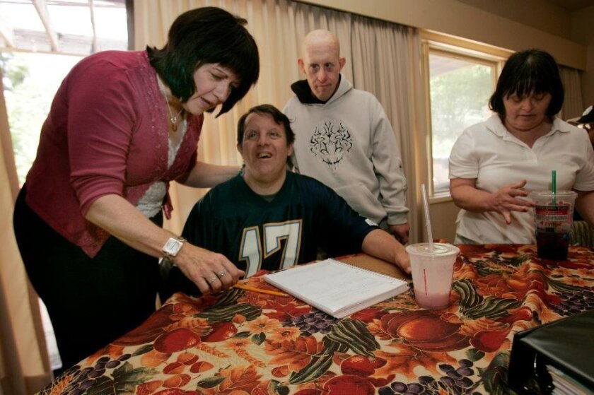 Molly Nocon (left) looks at a list of football teams that Noah Homes resident Gary Greco (center) is putting together. Looking on are Jack Bland and April Hennesy. The facility narrowly escaped state IOUs last year.