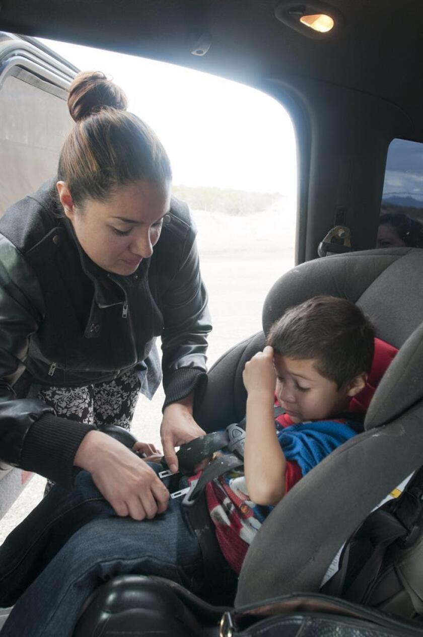 Una madre coloca a su hijo en un asiento protector dentro de su vehículo. EFE/Archivo