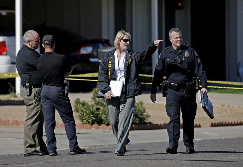 Officers investigate the scene of a fatal house fire and shooting Tuesday, Feb. 23, 2016, in Phoenix. Officers dodged bullets fired by the shooter and donned breathing gear to enter the burning home to help the victims. (AP Photo/Morry Gash)