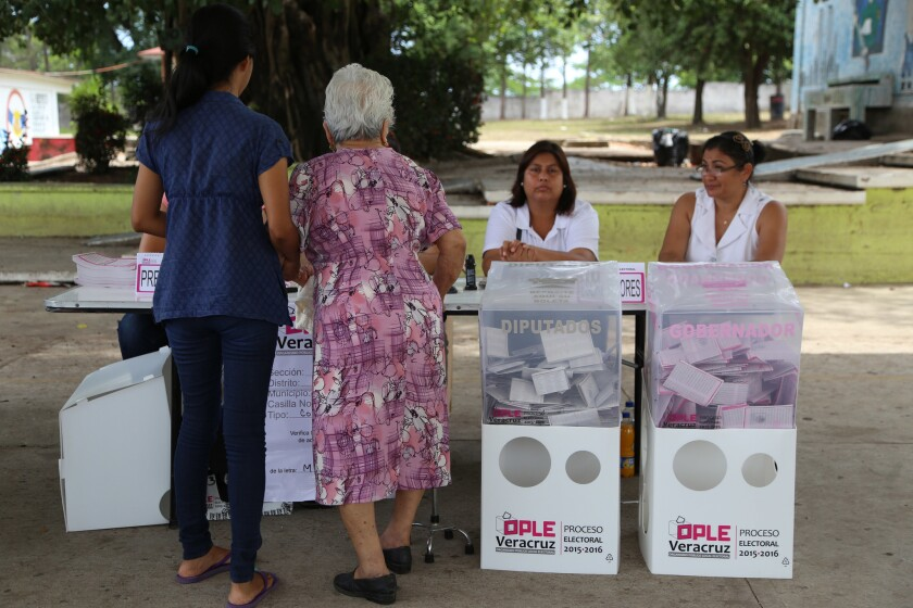 Dos mujeres se disponen a votar durante las elecciones para gobernador en Veracruz, México, el domingo 5 de junio de 2016. Doce estados en México votaron para elegir gobernador. (AP Foto/Ilse Huesca)