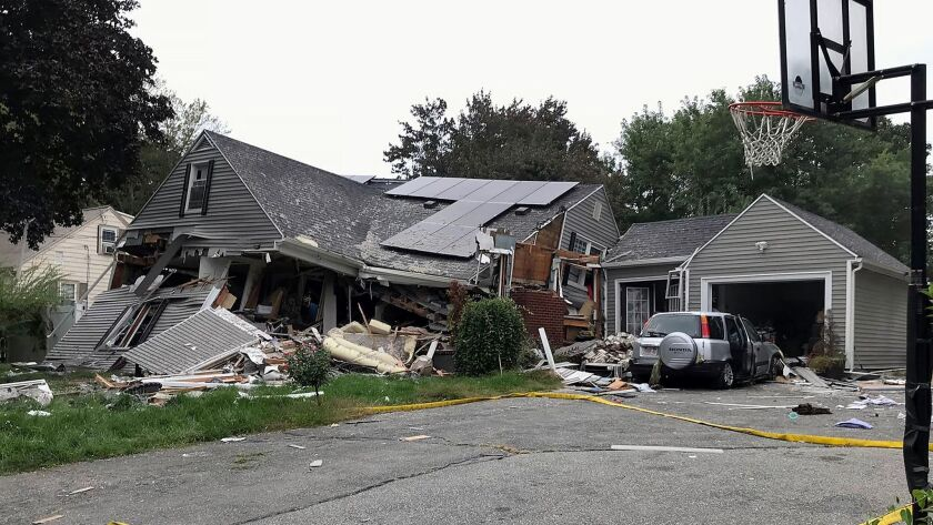 A collapsed home and car sit damaged Thursday in Lawrence, Mass., after a series of gas explosions in several communities north of Boston.