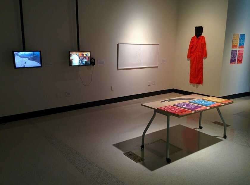 Exhibits inside an art show at UC San Diego supposedly feature items from the Guantanamo Bay Museum of Art and History and include an orange prison suit and videos about the detention center. All items were created by artists, and the museum is fictional.