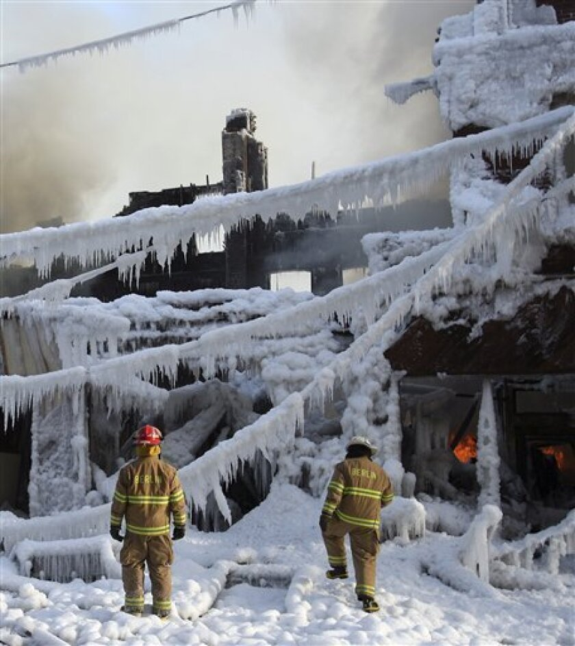 Firefighters inpect flames after an early morning fire fire broke out on Main Street. in sub-zero temperatures in Berlin, N.H., Saturday, Jan. 17, 2009. Bitter cold kept its grip on the Northeast on Saturday, while warmer temperatures brought relief to the Midwest and Southeast. (AP Photo/Jim Cole)