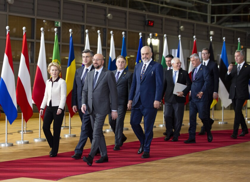 FILE- In this Sunday, Feb. 16, 2020 file photo, European Council President Charles Michel, right front, and European Commission President Ursula von der Leyen, front left, walk with leaders of the Western Balkans prior to a group photo at an EU-Western Balkans meeting at the Europa building in Brussels. The European Union's enlargement policy is at an impasse as its leaders gather for a summit focused on how to deal with Western Balkans neighbors that have been trying to enter the club for two decades. Meanwhile, the region is increasingly getting support from China and Russia instead.(AP Photo/Virginia Mayo, File)