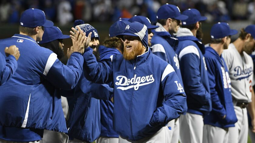 Los Angeles Dodgers third baseman Justin Turner, center, high fives his teammates