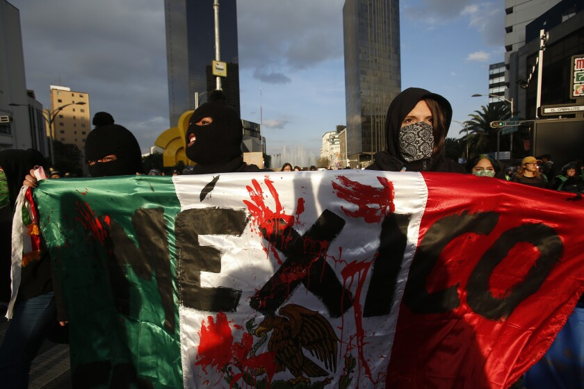 FILE - In this Jan. 25, 2020 file photo, masked, female protesters, holding a national flag marked with red stained handprints, march against the recent murder of two women, in Mexico City. Protests against gender violence in Mexico have intensified in recent years amid an increase in murders of women and girls. These killings are often accompanied by sexual assault and sometimes grisly mutilations. (AP Photo/Ginnette Riquelme, File)