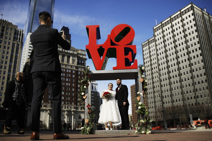 """FILE - In this Feb. 14, 2019 file photo, newlyweds Jennifer and Paul Raffa pose for a photograph under the Robert Indiana """"LOVE"""" sculpture at John F. Kennedy Plaza in Philadelphia on Valentine's Day. Indiana's estate has reached a settlement that keeps intact a longstanding relationship with the copyright holder of the iconic """"LOVE"""" series. Officials said Friday, June 11, 2021, that New York-based Morgan Art Foundation will work with the Maine-based Star of Hope Foundation, which aims to transform Indiana's island home in Maine into a museum. (AP Photo/Matt Rourke, File)"""
