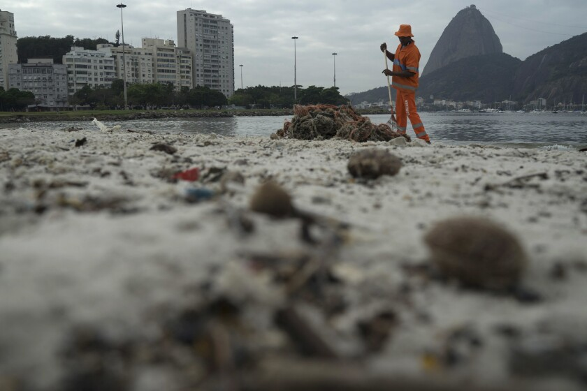 A worker removes trash from Botafogo beach next to the Sugarloaf Mountain and the Guanabara Bay in Rio de Janeiro. Just days ahead of the Olympic Games the waterways of Rio are as filthy as ever, contaminated with human sewage teeming with dangerous viruses and bacteria, according to a 16-month-long study commissioned by the Associated Press.