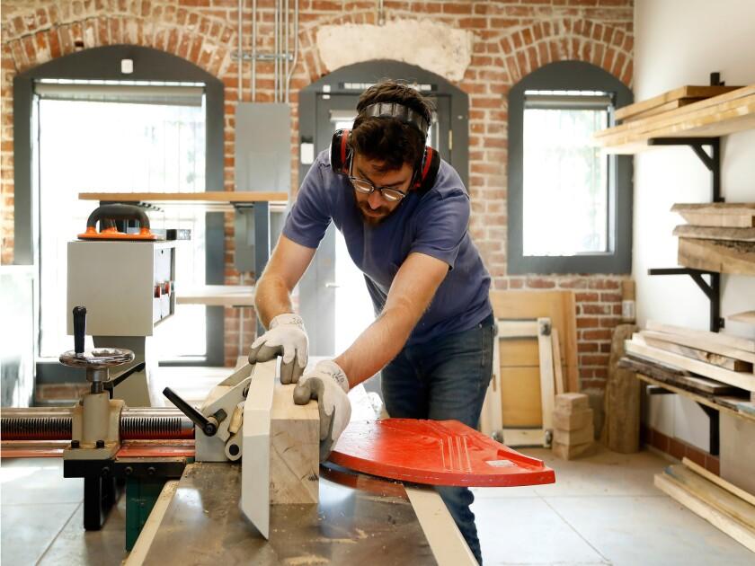 Josh Jackson works on custom furnishings for a restaurant in his Pasadena woodworking studio.