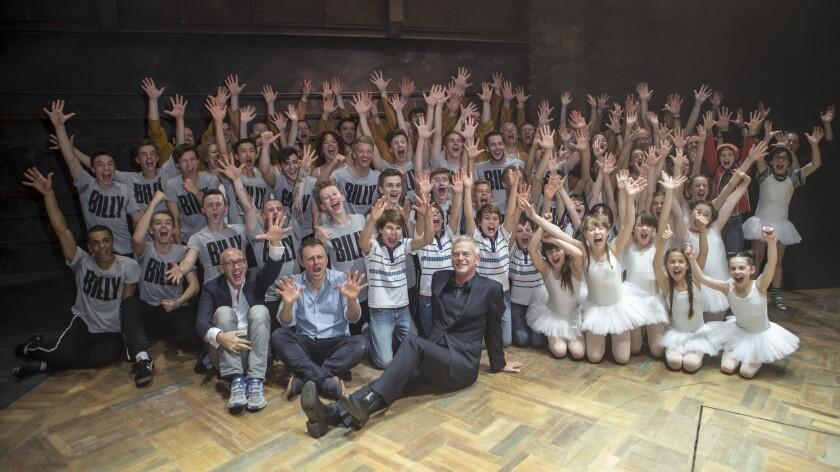 """Stephen Daldry, front, with former and present members of the """"Billy Elliot"""" cast."""