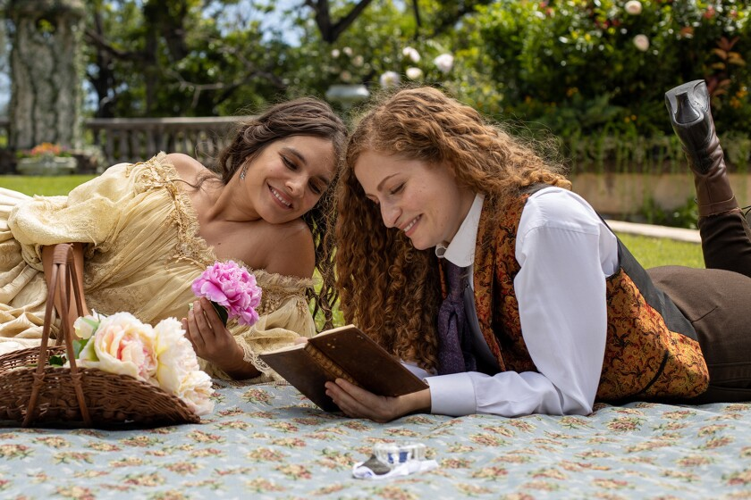 Two women look at an open book while lying on the ground on a blanket.