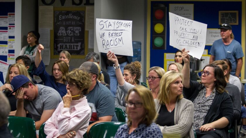 Trina Trac, left, and Rachel Potucek hold signs up during the public comments section of an Ocean Vi