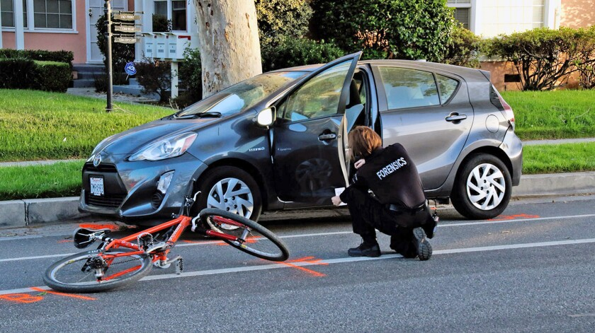 Burbank Police forensic specialist Carly Lott gathers evidence from the car door that was struck by the bicyclist.