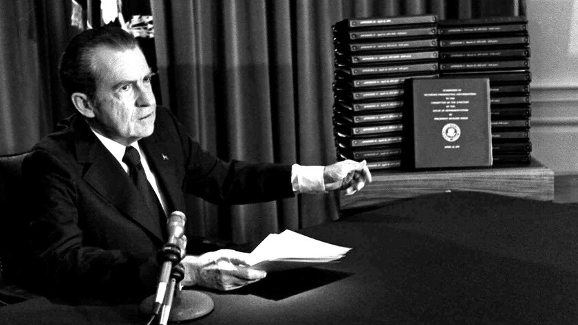 President Nixon gestures toward transcripts of White House tapes during an April 29, 1974, address in which he announced that he would turn over the transcripts to House impeachment investigators.