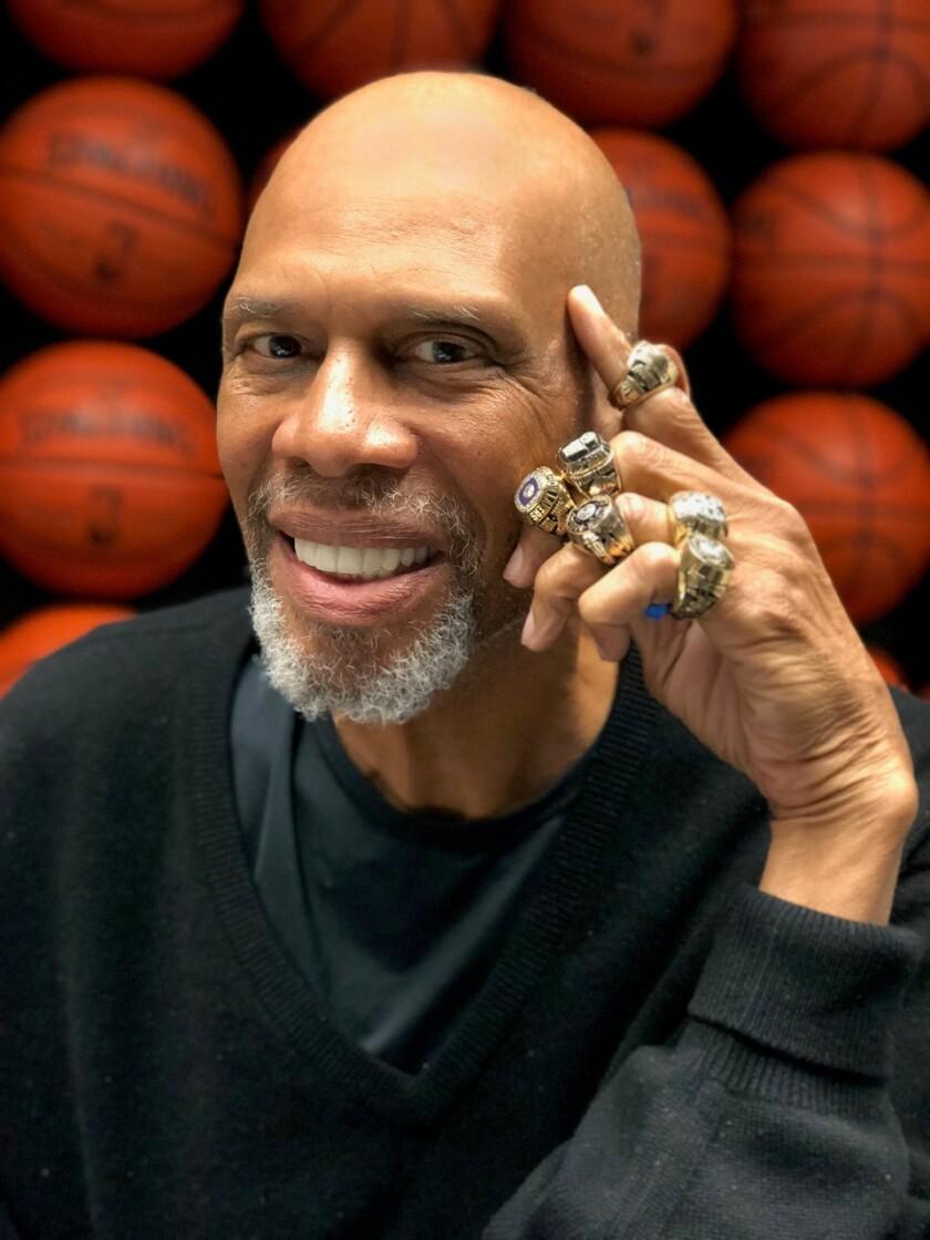 Lakers star Kareem Abdul-Jabbar poses with his championship rings.