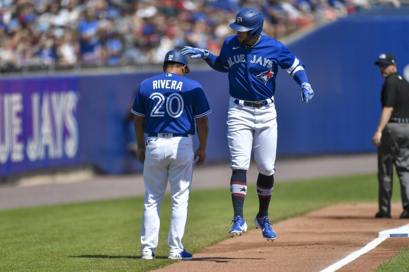Toronto Blue Jays' George Springer, right, taps third base coach Luis Rivera on the head while rounding the bases after hitting a solo home run against the Tampa Bay Rays during the second inning of a baseball game in Buffalo, N.Y., Saturday, July 3, 2021. (AP Photo/Adrian Kraus)