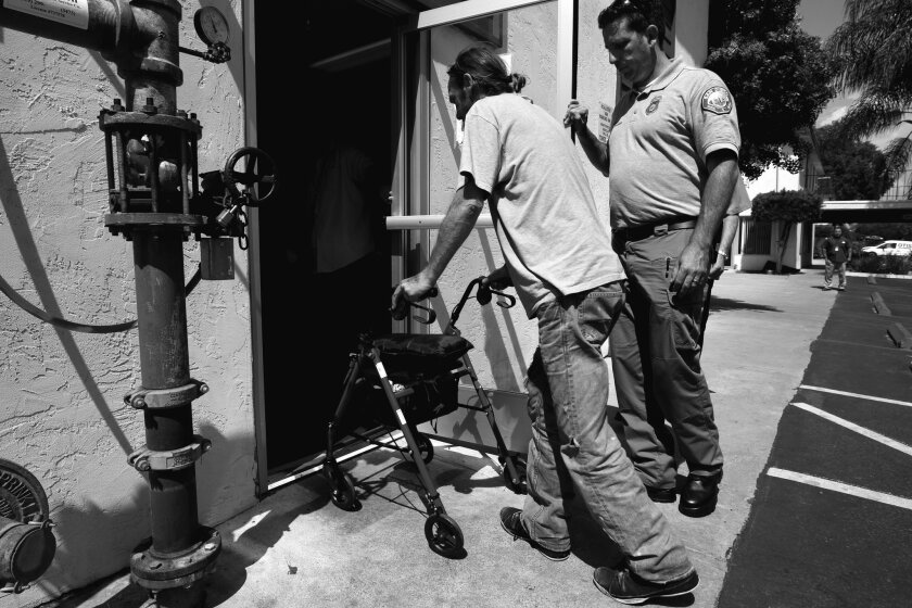 RAP Paramedic Shawn Percival holds the door open for Richard Collins, 42, who is homeless and a chronic alcoholic, as Collins checks into the McAlister Institute for their detox and treatment program.