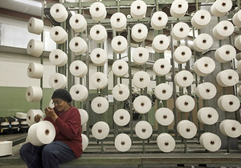 Wal-Mart announced a $10-million fund to spur U.S. manufacturing. Above, a worker in Georgia checks spools of yarn that will be woven into towels that will be sold at Wal-Mart.