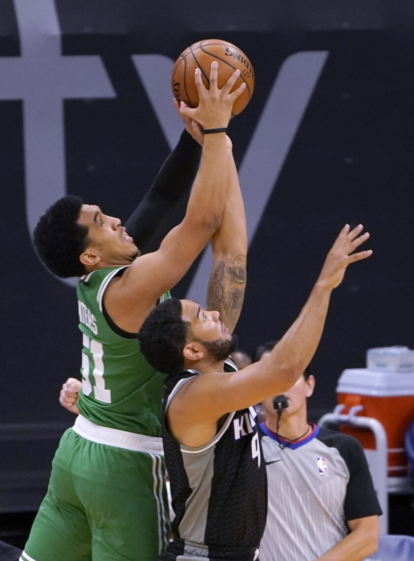 Boston Celtics guard Tremont Waters, left, and Sacramento Kings guard Cory Joseph reach for the ball during the first quarter of an NBA basketball game in Sacramento, Calif., Wednesday, Feb. 3, 2021. (AP Photo/Rich Pedroncelli)