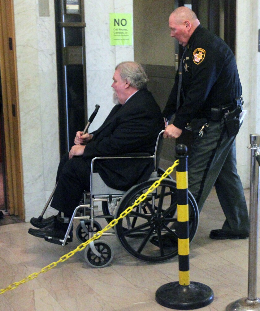 A Summit County sheriff's deputy wheels defendant Richard Beasley to the elevator at the conclusion of testimony in his murder trial in Summit County Court on Monday in Akron, Ohio.