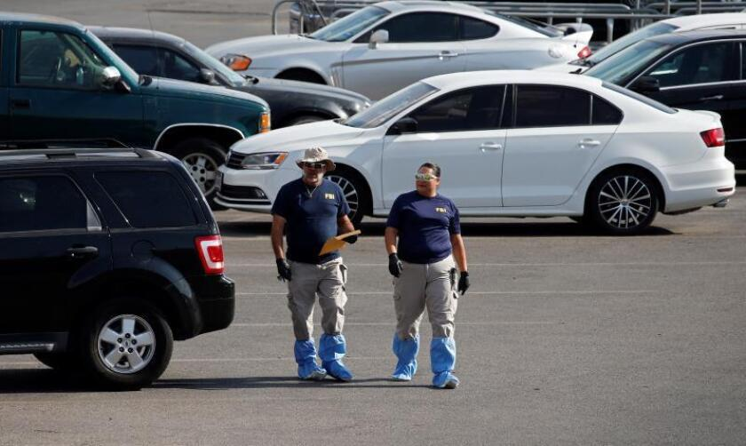 FBI agents look for cars to be removed from the crime scene and returned to their owners while investigating the mass shooting that happened at a Walmart in El Paso, Texas, 06 August 2019. EFE/EPA/Larry W. Smith