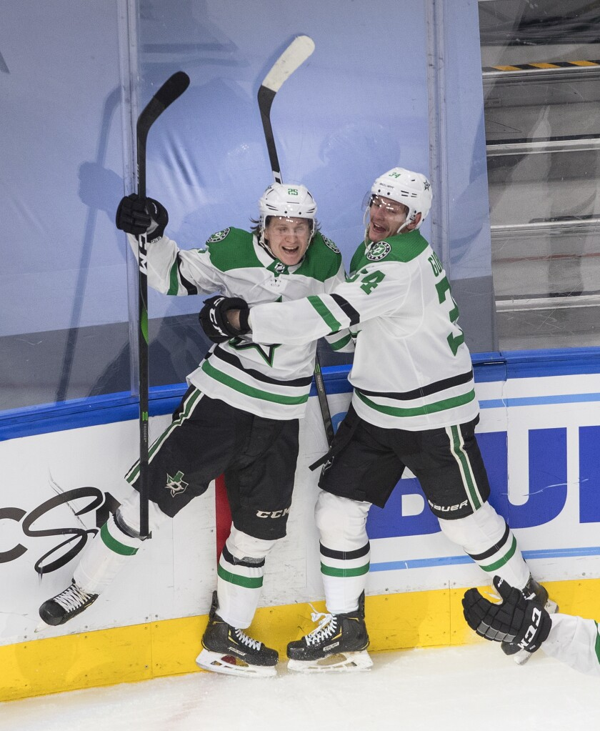 Dallas Stars' Joel Kiviranta (25) and Denis Gurianov (34) celebrate a goal against the Colorado Avalanche during third-period NHL Western Conference Stanley Cup playoff game action in Edmonton, Alberta, Friday, Sept. 4, 2020. (Jason Franson/The Canadian Press via AP)