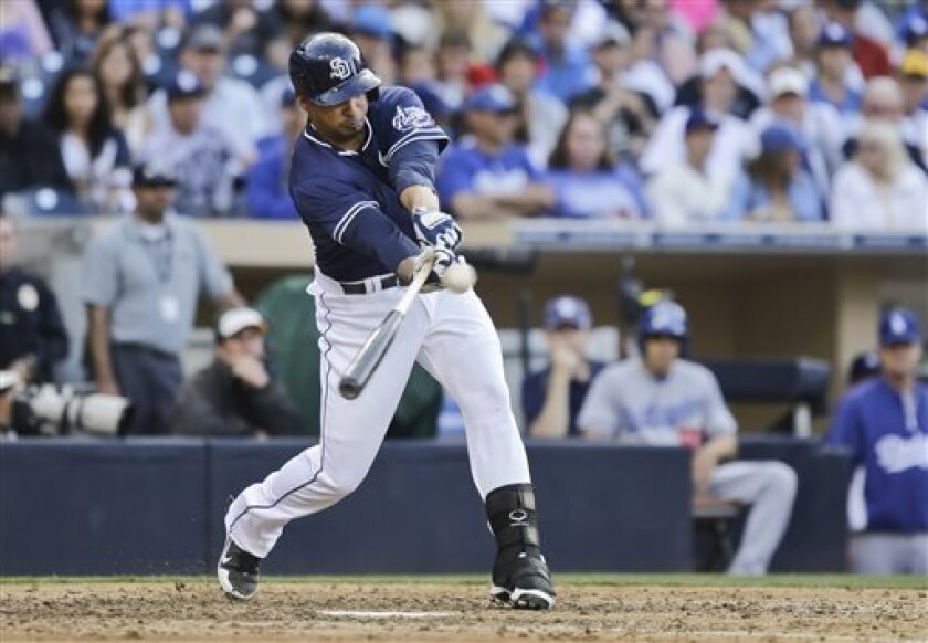 San Diego Padres' Jesus Guzman rips a double down the right field line to drive in Yasmani Grandal against the Los Angeles Dodgers in the eighth inning of a baseball game in San Diego, Saturday, June 22, 2013. (AP Photo/Lenny Ignelzi)