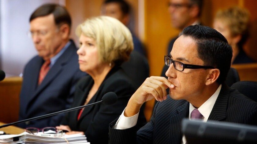 Former San Diego City Council President Todd Gloria, right, listens to public comment about former Mayor Bob Filner during a special meeting in the council chambers in San Diego on Aug. 23, 2013.
