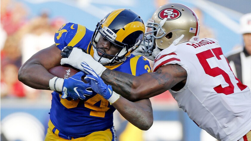 Rams running back Malcolm Brown is tackled by 49ers outside linebacker Eli Harold in the second half on Dec. 31, 2017.