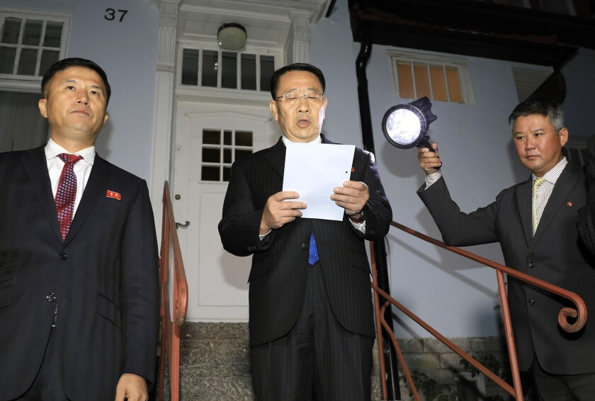 """North Korean negotiator Kim Miyong Gil, center, reads statement outside the North Korean Embassy in Stockholm, Sweden, Saturday, Oct. 5, 2019. North Korea's chief negotiator said Saturday that discussions with the U.S. on Pyongyang's nuclear program have broken down, but Washington said the two sides had """"good discussions"""" that it intends to build on in two weeks. (Kyodo News via AP)"""