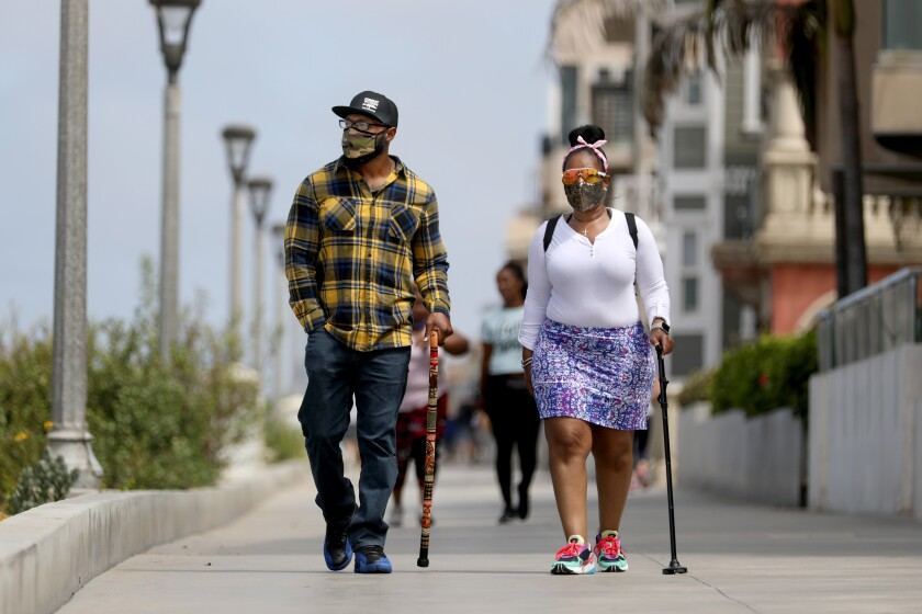 Anthony Mitchell and Anissa Randle of Los Angeles walk along the Strand in Manhattan Beach on July 3.