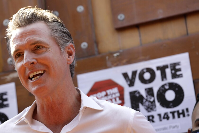 California Gov. Gavin Newsom stands in front of an anti-recall sign