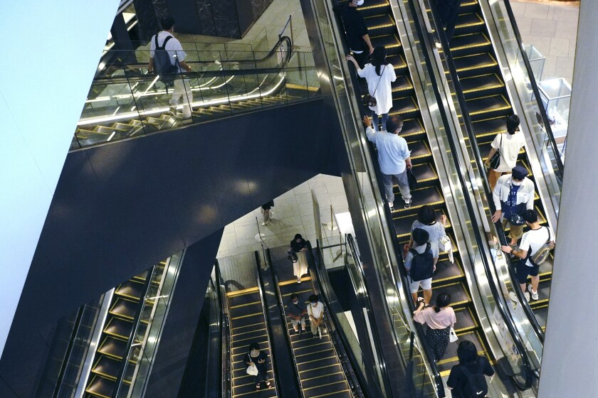 People ride escalators at a shopping mall in Tokyo on Aug. 24, 2020. Japan has reported its economy expanded at a 22.9% annual rate in the last quarter, as businesses and personal spending recovered from pandemic-related shocks in the spring and early summer. Economists said the upward revision released Tuesday, Dec. 8, 2020 was in line with forecasts and suggests Japan's economy, the world's third largest, is on the mend from the recession that started in late 2019, even before coronavirus outbreaks hit. (AP Photo/Eugene Hoshiko)