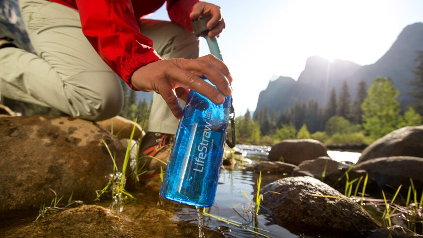 LifeStraw Reusable Water bottle with filtration straw near a stream. Credit: Adam Barker/LifeStraw