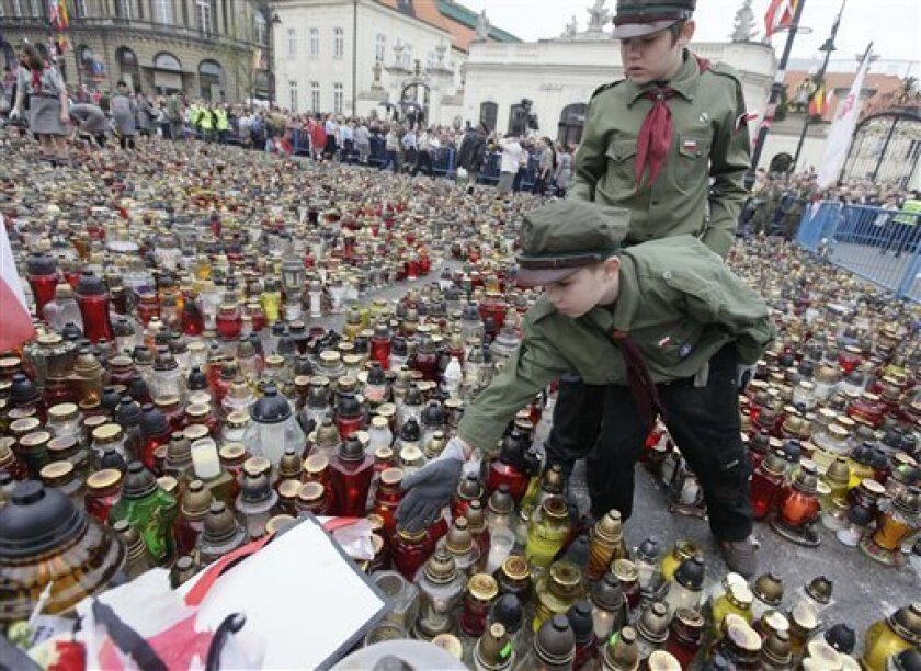 Boy scouts arrange candles in front of the Presidential palace on Friday, April 16, 2010 in Warsaw, Poland.  Polish President Lech Kaczynski who was killed in a plane crash in Russia is going to be buried in Krakow on Sunday.   (AP Photo/Czarek Sokolowski)