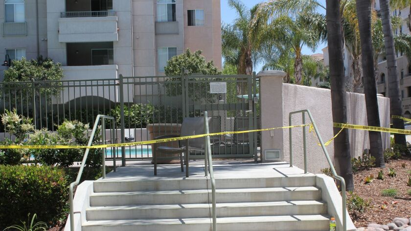 The La Jolla Crossroads apartment complex pool is closed off by police caution tape.