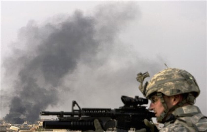 U.S Army Staff Sgt Brian Peterson from Karnes City, Texas, of 3rd Platoon, 302rd Military Police Company, aims with his rifle as black smoke fills the sky during a patrol, 360 kilometers, 225 miles, northwest of Baghdad, Iraq, Nov. 14, 2008. Strategically set, the country's third largest city, fixing embattled Mosul is not only vital in itself but a test of whether the Baghdad government can successfully grapple with potentially explosive forces beneath a still fragile stability achieved elsewhere in Iraq. (AP Photo/Petros Giannakouris)