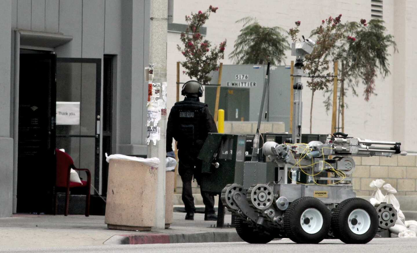 The L.A. County Sheriff's Department bomb squad was called to a Bank of America branch where a robbery occurred Wednesday morning in East Los Angeles. A manager at the bank was strapped with an apparent explosive device and forced to help two men rob her own bank. She followed instructions to throw the money out the bank's door. The robbers escaped.