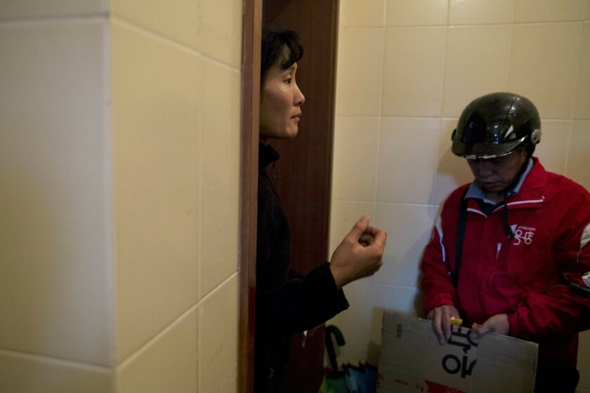 """In this Thursday, Nov. 12, 2015, photo, a Yihaodian delivery man, at right, delivers his goods to a customer, Ms. Huang, in Shanghai. """"I seldom go to the shopping mall or supermarket. Mainly online,"""" said Huang. (AP Photo/Ng Han Guan)"""
