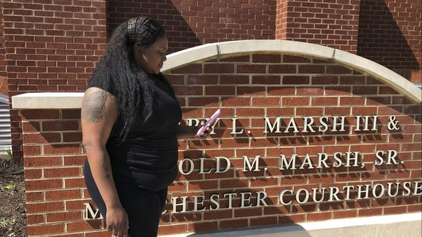 Strangé Simon, 25, stands outside a courthouse on April 16, 2019 in Richmond, Va. Simon attended a recent hearing in her marijuana possession case. Simon said receiving text reminders from the public defender's office stopped her from showing up for court on the wrong day.